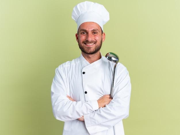Uśmiechnięty młody kaukaski kucharz w mundurze szefa kuchni i czapce stojącej z zamkniętą postawą trzymając kadzi, patrząc na kamerę odizolowaną na oliwkowozielonej ścianie
