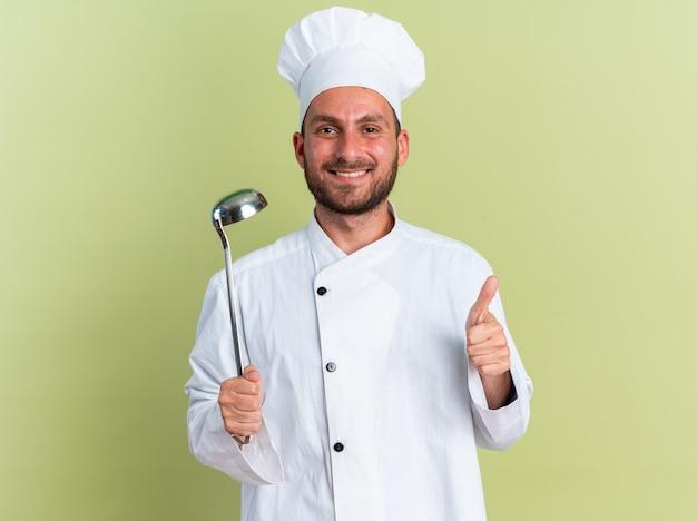 Uśmiechnięty młody kaukaski kucharz w mundurze szefa kuchni i czapce trzymającej kadzi, patrząc na kamerę pokazującą kciuk na białym tle na oliwkowozielonej ścianie