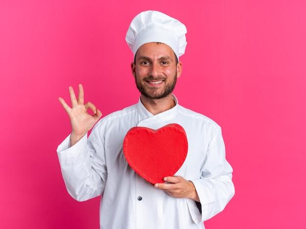 Uśmiechnięty młody kaukaski kucharz w mundurze szefa kuchni i czapce trzymającej kształt serca, patrząc na kamerę robi ok znak na różowej ścianie
