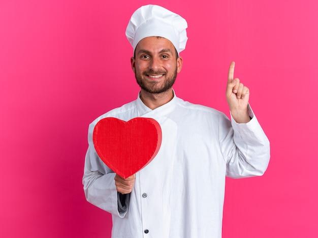 Uśmiechnięty młody kaukaski kucharz w mundurze szefa kuchni i czapce trzymającej kształt serca skierowany w górę