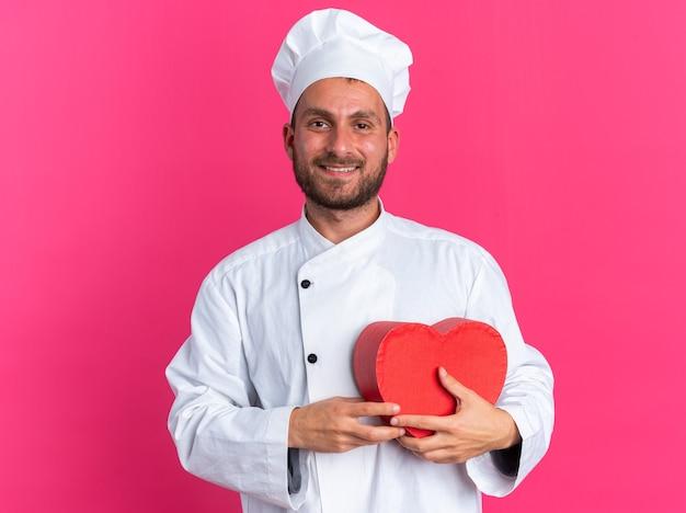 Uśmiechnięty młody kaukaski kucharz w mundurze szefa kuchni i czapce trzymającej kształt serca
