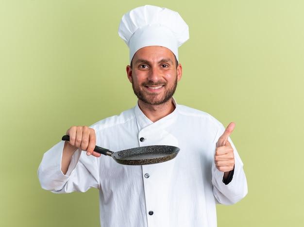 Uśmiechnięty młody kaukaski kucharz w mundurze szefa kuchni i czapce trzymającej patelnię, patrząc na kamerę pokazującą kciuk na białym tle na oliwkowozielonej ścianie