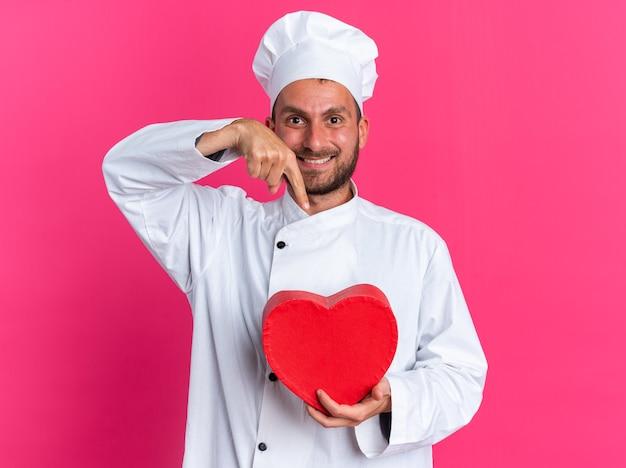 Uśmiechnięty młody kaukaski kucharz w mundurze szefa kuchni i czapce, trzymający i wskazujący na kształt serca, patrzący na kamerę odizolowaną na różowej ścianie