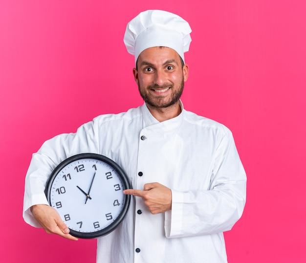 Uśmiechnięty młody kaukaski kucharz w mundurze szefa kuchni i czapce, trzymający i wskazujący na zegar, patrzący na kamerę odizolowaną na różowej ścianie