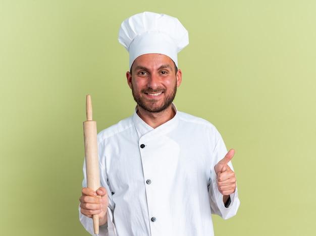 Uśmiechnięty młody kaukaski kucharz w mundurze szefa kuchni i czapce, trzymający wałek do ciasta, patrzący na kamerę pokazującą kciuk w górę na oliwkowo-zielonej ścianie