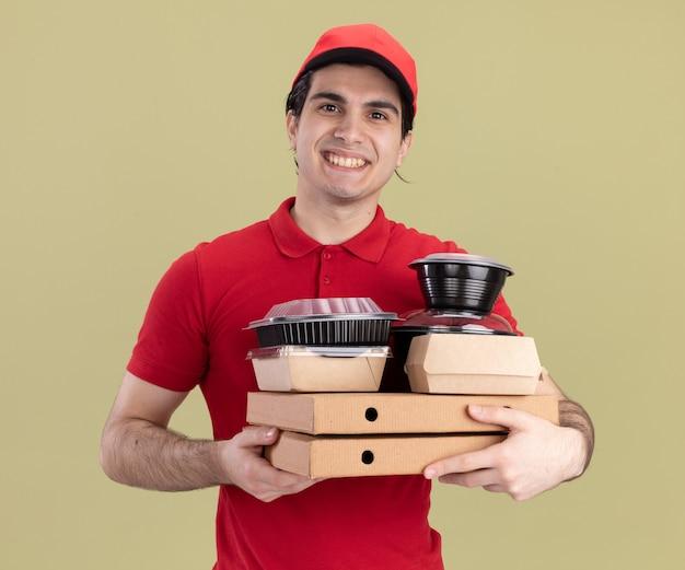 Uśmiechnięty młody kaukaski mężczyzna dostarczający w czerwonym mundurze i czapce trzymający paczki pizzy z pojemnikami na żywność i papierowymi opakowaniami żywności na nich odizolowanymi na oliwkowozielonej ścianie