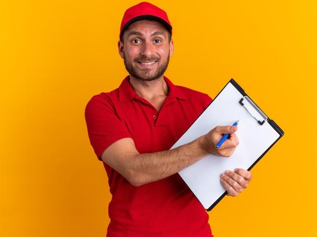 Uśmiechnięty młody kaukaski mężczyzna dostawy w czerwonym mundurze i czapce patrząc na kamerę pokazującą schowek wskazujący na nim pióro na białym tle na pomarańczowej ścianie