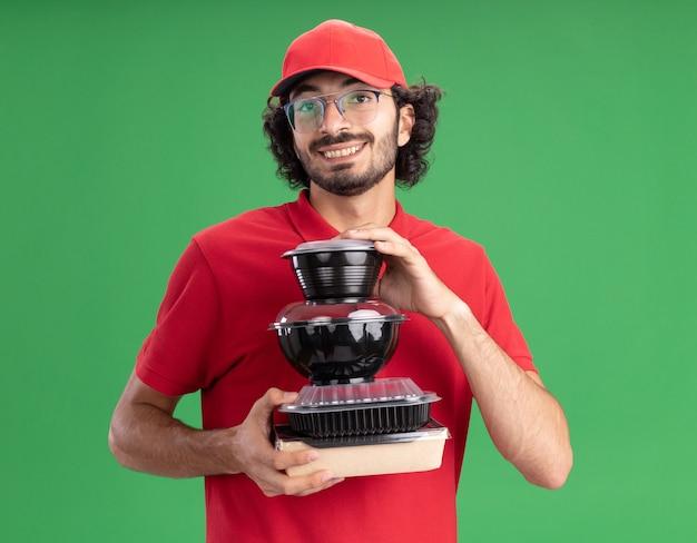 Uśmiechnięty młody kaukaski mężczyzna dostawy w czerwonym mundurze i czapce w okularach trzymających papierowe opakowanie żywności i pojemniki na żywność izolowane na zielonej ścianie