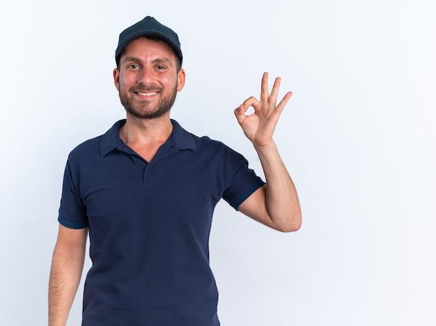 Uśmiechnięty młody kaukaski mężczyzna dostawy w niebieskim mundurze i czapce, patrząc na kamerę robi ok znak na białej ścianie z miejscem na kopię