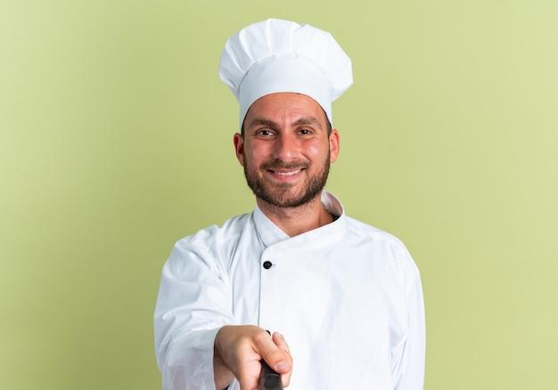 Uśmiechnięty młody kaukaski mężczyzna kucharz w mundurze szefa kuchni i czapce, patrząc na kamerę wyciągającą patelnię w kierunku kamery odizolowaną na oliwkowozielonej ścianie