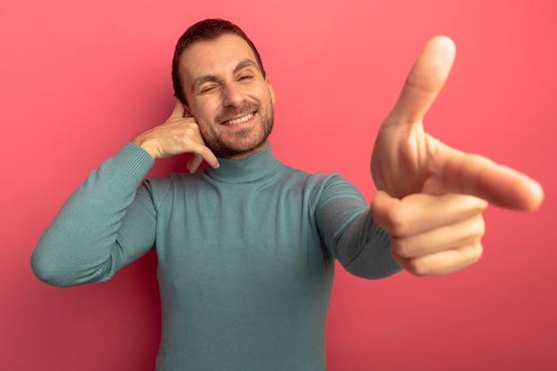 Uśmiechnięty młody kaukaski mężczyzna mruga, robi gesty połączeń i pistoletów na białym tle na szkarłatnej ścianie