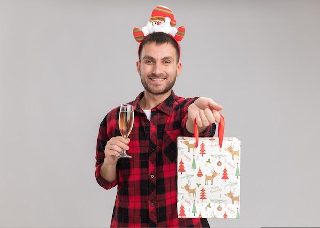 Uśmiechnięty młody kaukaski mężczyzna noszący świąteczną opaskę trzymającą kieliszek szampana patrzący rozciągający się świąteczny prezent w torbie w kierunku kamery na białym tle na białej ścianie z miejscem na kopię