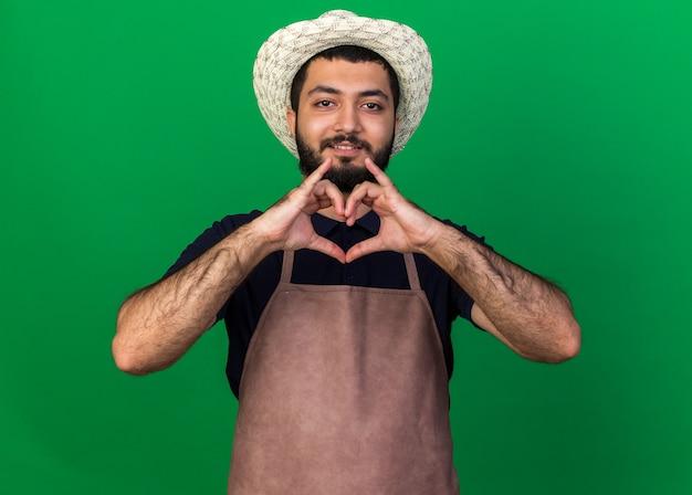 Uśmiechnięty młody kaukaski mężczyzna ogrodnik w kapeluszu ogrodniczym gestykulujący znak serca na zielonej ścianie z kopią miejsca
