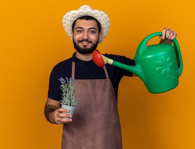 Uśmiechnięty młody kaukaski mężczyzna ogrodnik w kapeluszu ogrodniczym udając podlewanie kwiatów w doniczce z konewką odizolowaną na pomarańczowej ścianie z kopią przestrzeni