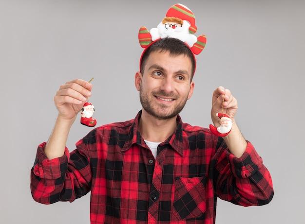 Uśmiechnięty młody kaukaski mężczyzna ubrany w opaskę świętego mikołaja trzymając santa claus ozdoby świąteczne patrząc na bok na białym tle