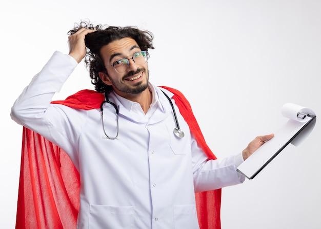 Uśmiechnięty młody kaukaski mężczyzna w okularach optycznych w mundurze lekarza z czerwonym płaszczem i stetoskopem na szyi podnosi włosy ręką i trzyma schowek na białej ścianie