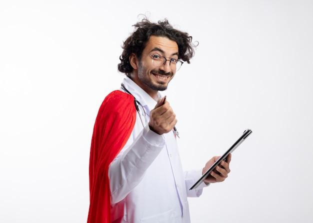 Uśmiechnięty młody kaukaski mężczyzna w okularach optycznych w mundurze lekarza z czerwonym płaszczem i stetoskopem na szyi stoi bokiem trzymając schowek i wskazując ołówkiem
