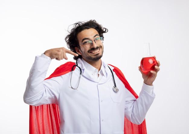 Uśmiechnięty młody kaukaski mężczyzna w okularach optycznych w mundurze lekarza z czerwonym płaszczem i stetoskopem na szyi trzyma i wskazuje czerwony płyn chemiczny w szklanej kolbie na białej ścianie
