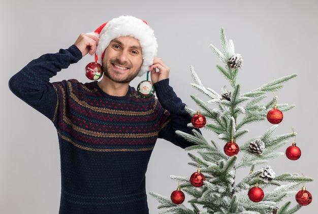 Uśmiechnięty młody kaukaski mężczyzna w świątecznym kapeluszu stojącym w pobliżu choinki, patrzący trzymający bombki w pobliżu uszu odizolowanych na białej ścianie
