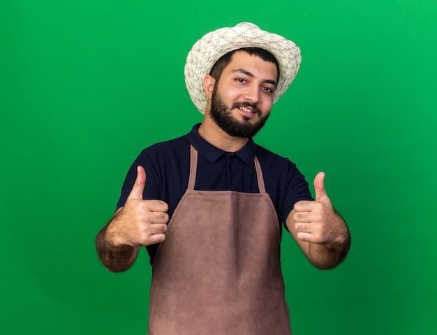 Uśmiechnięty młody kaukaski ogrodnik męski na sobie kapelusz ogrodniczy kciuki do góry z dwóch rąk na białym tle na zielonej ścianie z miejsca na kopię