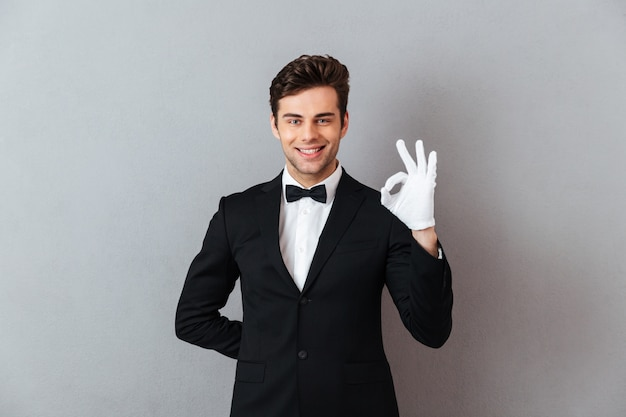 Uśmiechnięty młody kelner pokazuje zadowalającego gest.