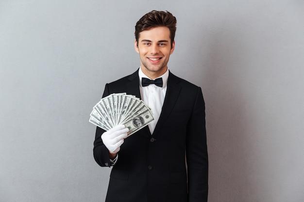 Uśmiechnięty młody kelner trzyma pieniądze.