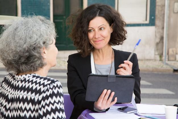 Uśmiechnięty młody konsultant oferuje pióro do starszych klientów