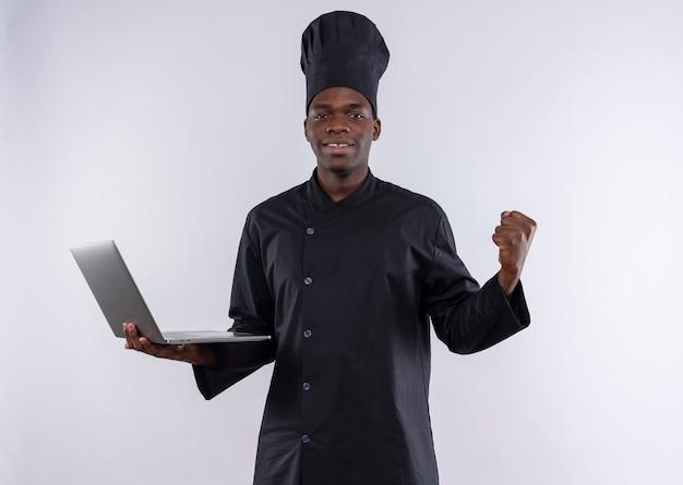 Uśmiechnięty młody kucharz afro-amerykański w mundurze szefa kuchni trzyma laptopa i trzyma pięść na białym z miejsca na kopię