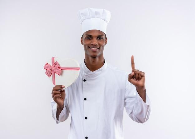 Uśmiechnięty młody kucharz afro-amerykański w mundurze szefa kuchni trzyma pudełko w kształcie serca i wskazuje na białym tle na białym tle z miejsca na kopię