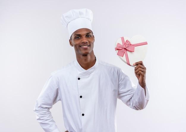 Uśmiechnięty młody kucharz afro-amerykański w mundurze szefa kuchni trzyma pudełko w kształcie serca na białym tle na białym tle z miejsca na kopię