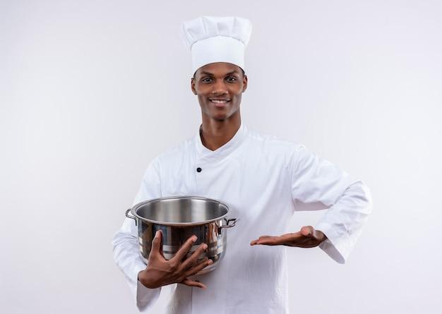 Uśmiechnięty młody kucharz afro-amerykański w mundurze szefa kuchni trzyma rondel i trzyma rękę prosto na na białym tle z miejsca na kopię