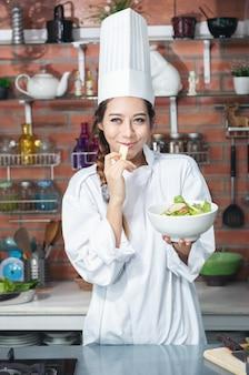 Uśmiechnięty młody kucharz azjatyckich kobieta w białym mundurze stoi w kuchni, pokazując sałatkę w misce i czerwone jabłko na dłoni.