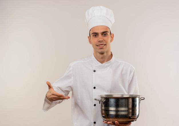 Uśmiechnięty młody kucharz mężczyzna ubrany w mundur szefa kuchni pokazując rondel w ręku z miejsca na kopię