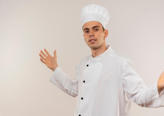 Uśmiechnięty młody kucharz mężczyzna ubrany w mundur szefa kuchni rozkłada ręce z miejsca na kopię