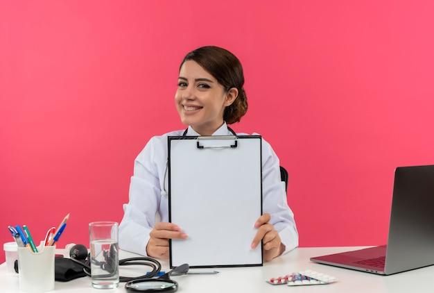 Uśmiechnięty młody lekarz kobiet na sobie szatę medyczną ze stetoskopem siedzi przy biurku na komputerze z narzędzi medycznych, trzymając schowek z miejsca na kopię