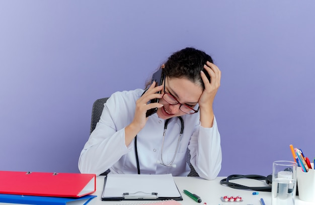 Uśmiechnięty młody lekarz kobiet na sobie szlafrok medyczny i stetoskop siedzi przy biurku z narzędzi medycznych rozmawia przez telefon patrząc w dół dotykając głowy na białym tle