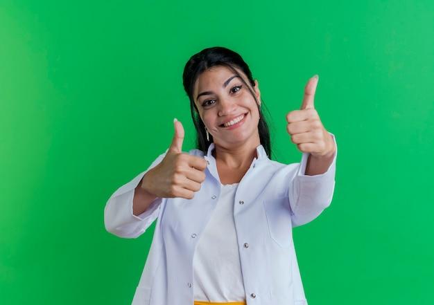 Uśmiechnięty Młody Lekarz Kobiet Na Sobie Szlafrok Medyczny Pokazujący Kciuki Do Góry Na Białym Tle Na Zielonej ścianie Z Miejsca Na Kopię Darmowe Zdjęcia