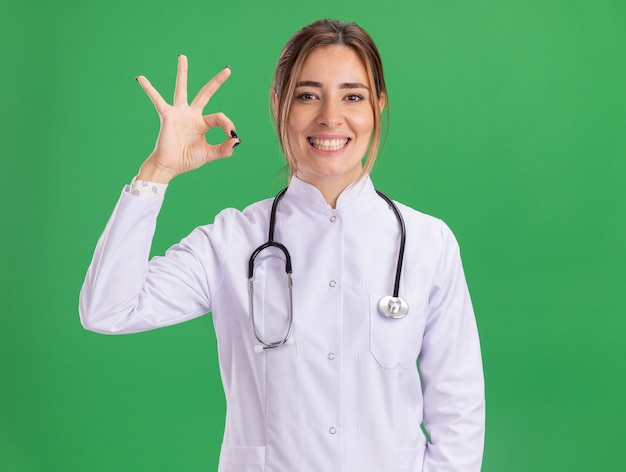 Uśmiechnięty młody lekarz kobiet na sobie szlafrok medyczny ze stetoskopem, pokazując w porządku gest na białym tle na zielonej ścianie