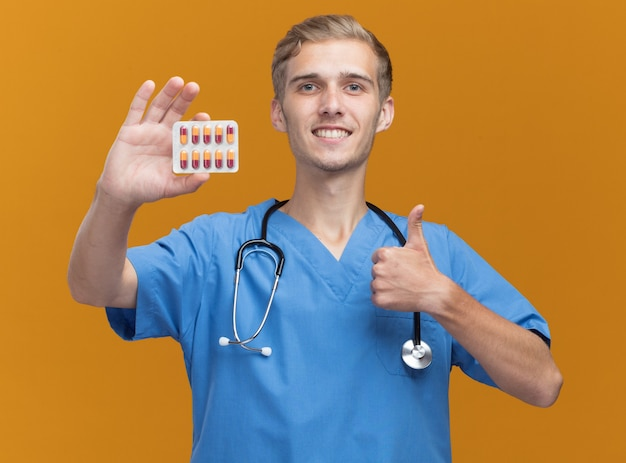 Uśmiechnięty młody lekarz mężczyzna ubrany w mundur lekarza ze stetoskopem trzymając pigułki pokazując kciuk do góry na białym tle na pomarańczowej ścianie