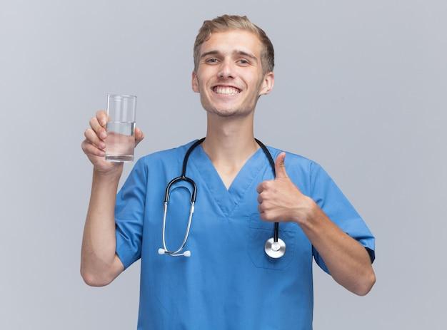 Uśmiechnięty młody lekarz mężczyzna ubrany w mundur lekarza ze stetoskopem trzymając szklankę wody pokazując kciuk do góry na białym tle na białej ścianie