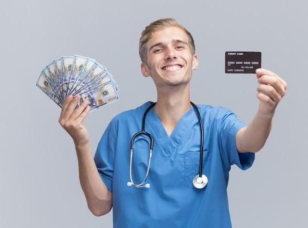 Uśmiechnięty młody lekarz mężczyzna ubrany w mundur lekarza ze stetoskopem, trzymający gotówkę i kartę kredytową w aparacie na białym tle na białej ścianie
