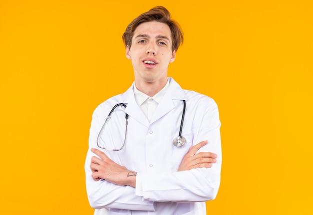 Uśmiechnięty młody lekarz mężczyzna ubrany w szatę medyczną ze stetoskopem krzyżującym ręce