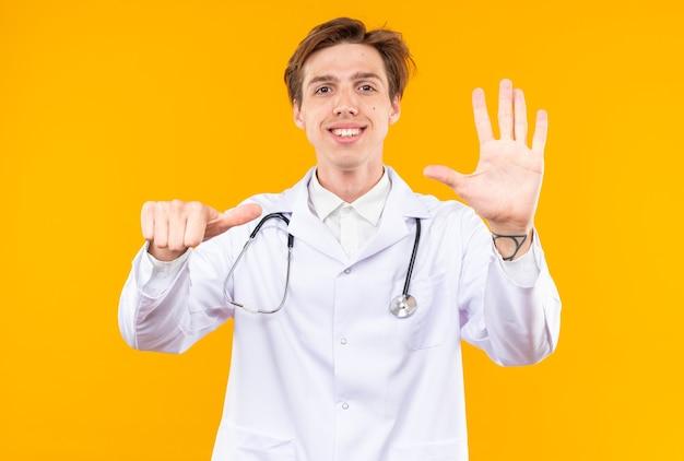 Uśmiechnięty młody lekarz mężczyzna ubrany w szatę medyczną ze stetoskopem pokazującym gest różnie