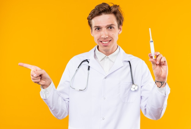 Uśmiechnięty młody lekarz mężczyzna ubrany w szatę medyczną ze stetoskopem, trzymający punkty strzykawki z boku