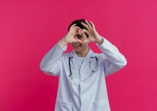 Uśmiechnięty młody lekarz mężczyzna ubrany w szlafrok medyczny i stetoskop robi znak serca na białym tle na różowej ścianie z miejsca na kopię