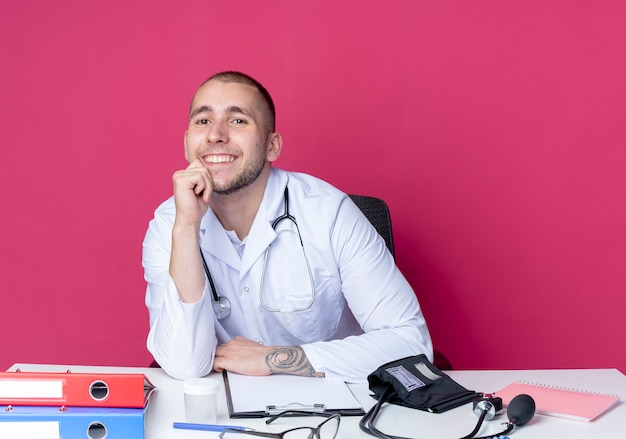 Uśmiechnięty młody lekarz mężczyzna ubrany w szlafrok medyczny i stetoskop siedzi przy biurku z narzędziami pracy, kładąc rękę na brodzie na białym tle na różowej ścianie