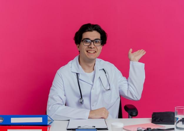 Uśmiechnięty młody lekarz mężczyzna ubrany w szlafrok medyczny i stetoskop w okularach siedzi przy biurku z narzędziami medycznymi pokazując pustą rękę na białym tle na różowej ścianie