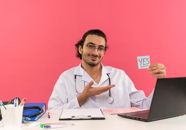 Uśmiechnięty młody lekarz mężczyzna z okularami medycznymi na sobie szatę medyczną ze stetoskopem