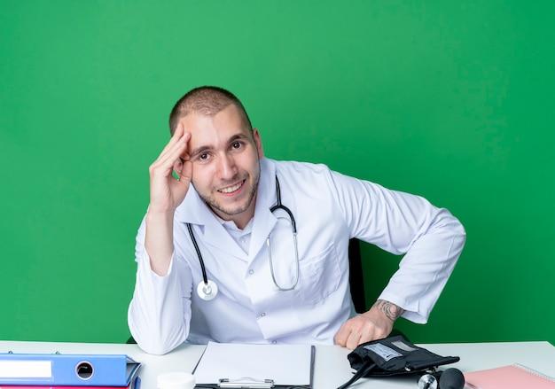 Uśmiechnięty młody lekarz płci męskiej ubrany w szlafrok i stetoskop siedzi przy biurku z narzędziami pracy, kładąc rękę na głowie na białym tle na zielonej ścianie