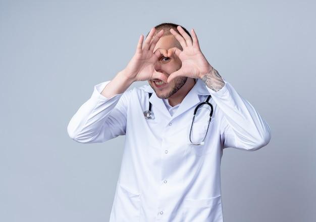 Uśmiechnięty młody lekarz płci męskiej ubrany w szlafrok medyczny i stetoskop na szyi robi znak serca i patrzy z przodu przez niego na białym tle na białej ścianie